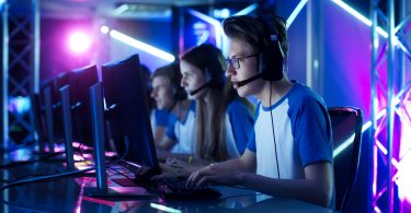 Team of Teenage Gamers Play in Multiplayer PC Video Game on a eSport Tournament. Captain Gives Commands into Microphone, Trying Strategically Win the Game.